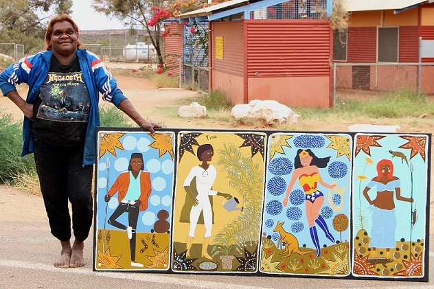 Artist Kaylene Whiskey stands outside an arts centre in Indulkana with a painting.