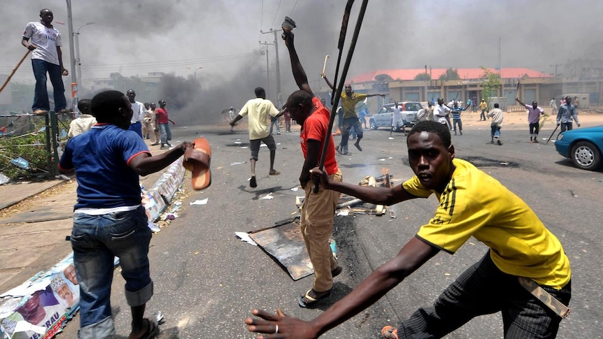 People holding wooden and metal sticks demonstrate in Nigeria's northern city of Kano. (AFP)