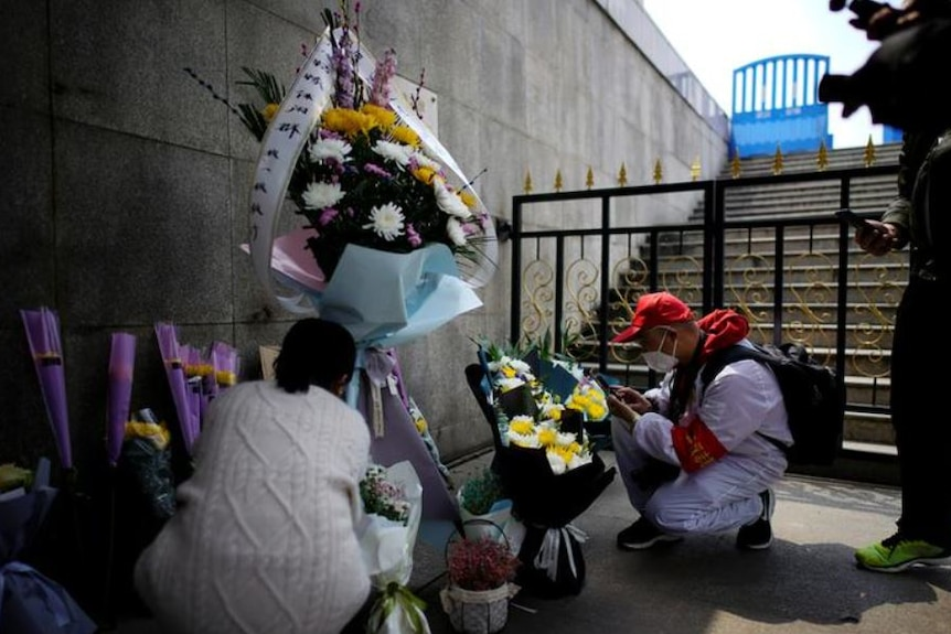 People lay flowers to remember the dead.