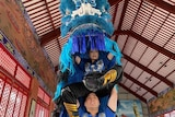 Anna Duong and Albert Nguyen are dressed in a blue lion dancing costume.