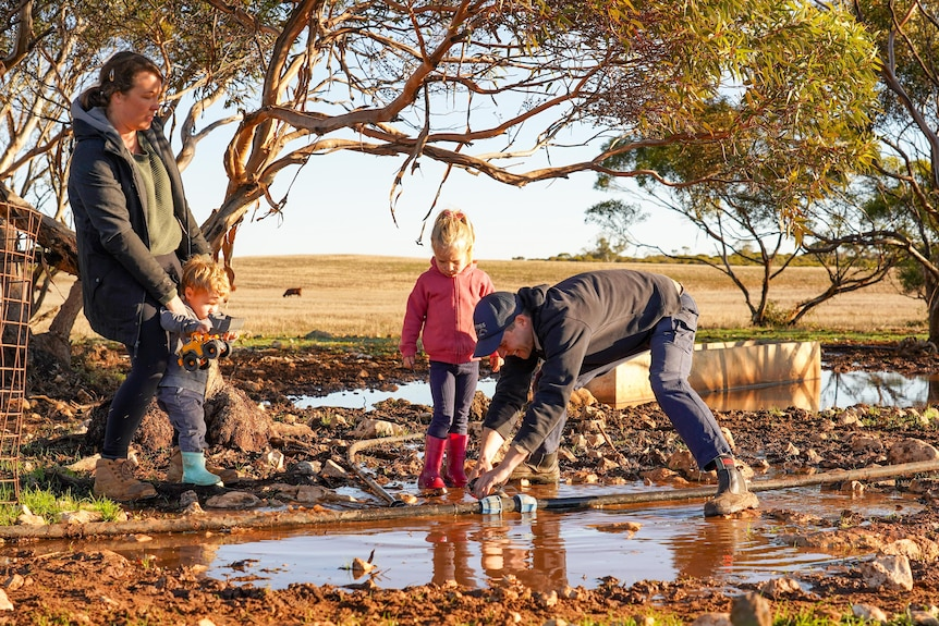 A man, woman and two children watch as the man fixes a hose outdoors