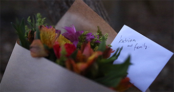 Flowers and a hand written card are placed near the house where seven people were killed.