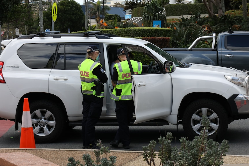 Two police in high visibility yellow vests speak to a person inside a white car