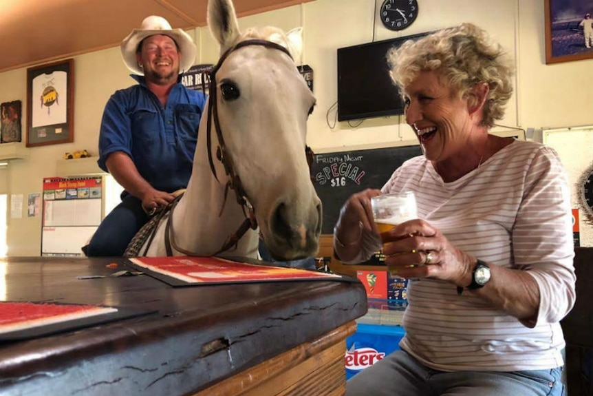 Ewart with beer at bar looking at horse in pub with man on its back.