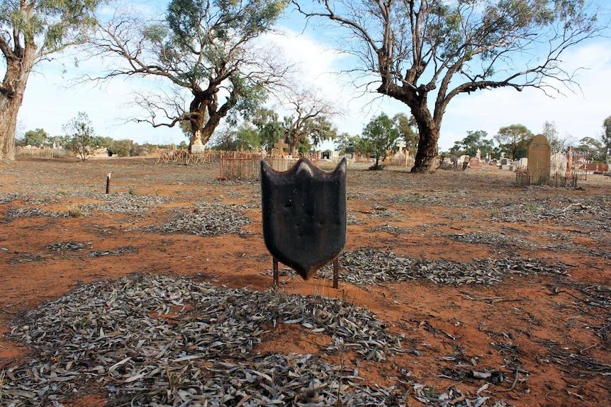 An unknown grave marked by a black shield shape marker in a bush landscape.