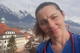 A woman wearing scrubs and a stethoscope posses in front of the Alps