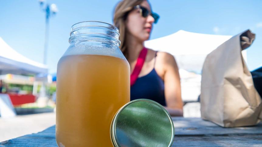 A jar of kombucha on a table at a farmer's market.
