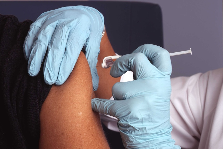 Close up of gloved hands injecting a vaccination into someone's upper arm.