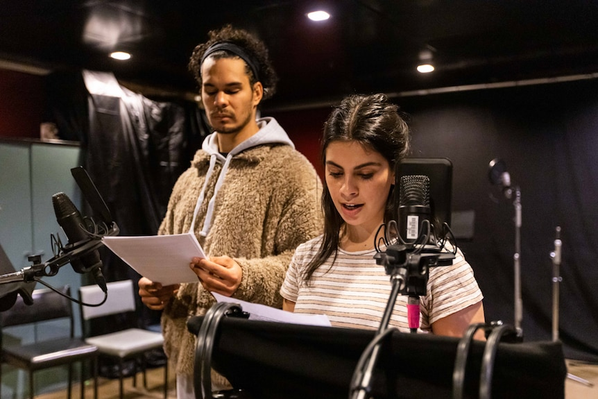 A tall young man with fluffy jacket stands next to young woman in sound recording studio, both in front of mics.