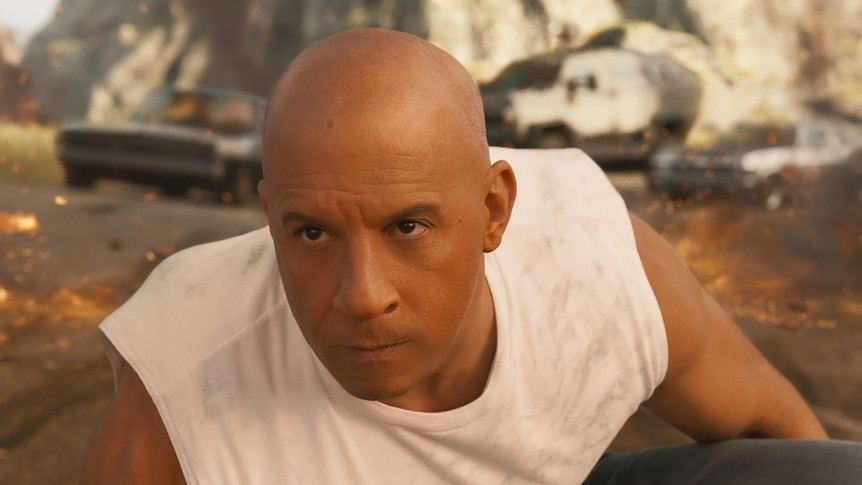 Vin Diesel crouched in front of three cars, with a determined expression, in Fast and Furious 9