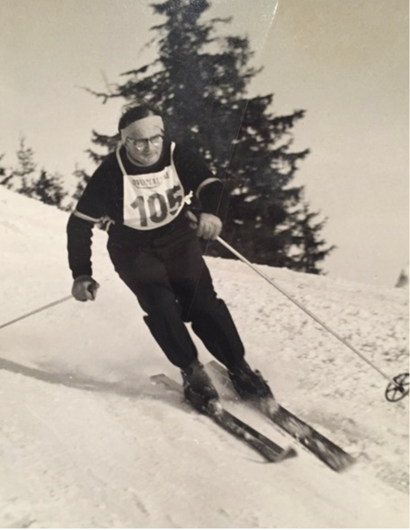 A black and white photo of a man skiing downhill with the number 105 on his chest