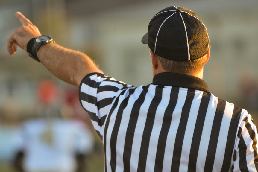 A sports umpire or referee, wearing a black and white uniform, points his finger.