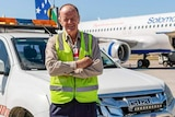 Man standing in front of a car and airplane.