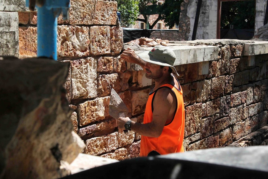 a man with stone on a building site