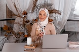 A womn sitting with a laptop open on her desk