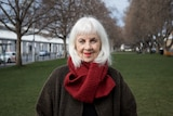 A white woman in her mid 70s with white hair and red scarf and brown winter jacket stands in a green park