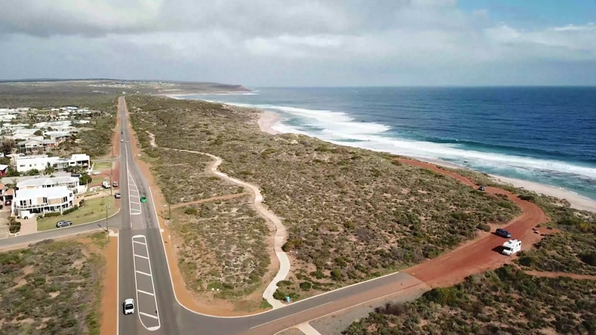 An aerial drone photo of a regional coastline, with red dirt and shrubs meeting cliffs and ocean.