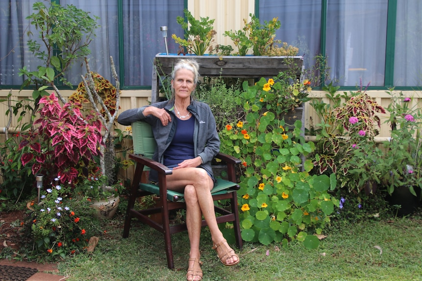 Jenny Sadar sitting on a chair in her her garden outside of her caravan