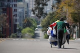 A homeless man pushes a cart full of his belongings along an empty street.