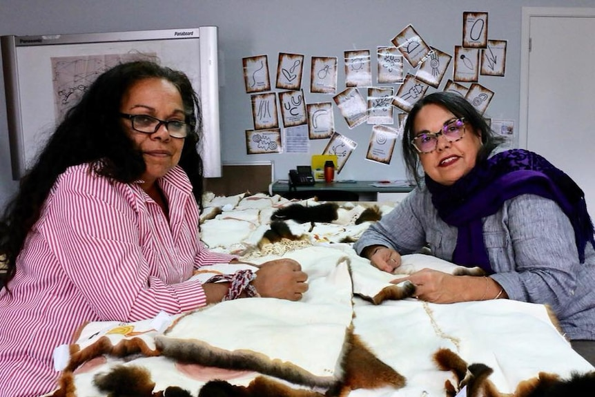 Two Aboriginal women working at a table sewing together squares of possum skin