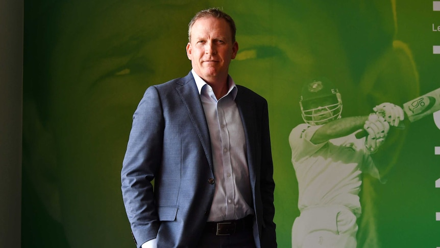 An Australian cricket executive stands in front of a photo portrait of Ricky Ponting.