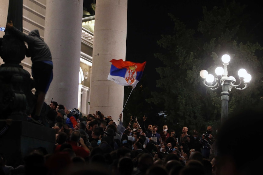 A mob gathers waiving a single flag on the steps of a government building with large white marble columns.