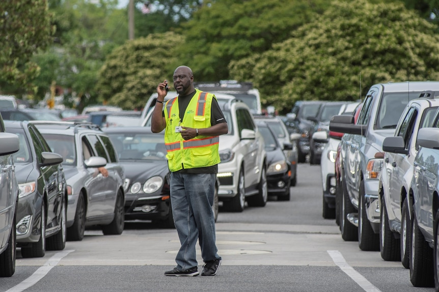 Cars queue for petrol in the US amid a fuel shortage, while an attendant supervises.