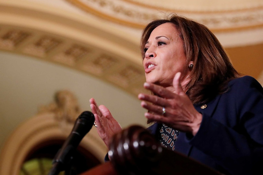 Kamala Harris stands at a lectern, gesturing with her hands and talking to reporters.