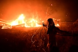 The silhouette of a man pulling a hose is backlit by a structure on fire behind him