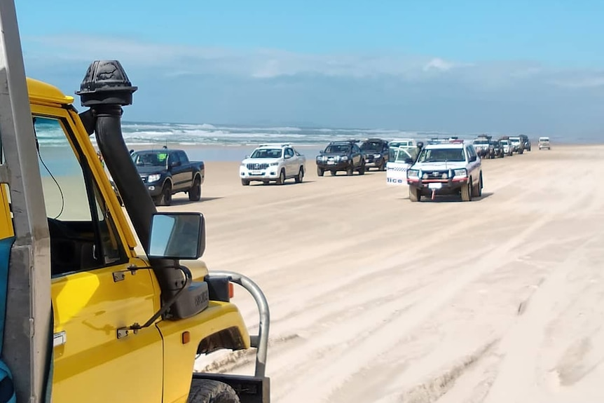 Line of four wheel drives along the beach with police driving along side