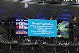 """A screen at Perth Stadium says """"Severe Weather"""" as players mill around on the field"""