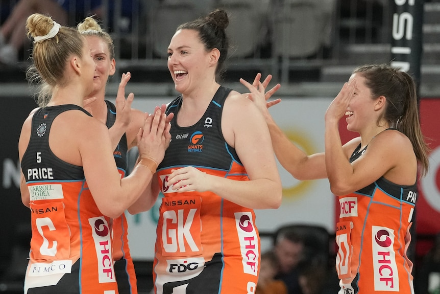 A group of Giants Super Netball players congratulate each other.