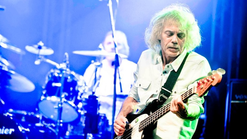 An elderly man with white curly hair plays bass guitar in front of a drummer on a brightly lit stage.