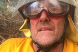 Close up of face ofexhausted firefighter in the midst of fighting a bushfire
