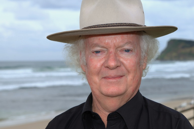 A portrait shot of a man in a black shirt and felt hat with the beach in the background