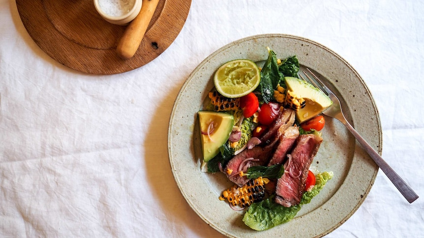 A plate of steak salad with medium rare sliced steak, cos lettuce, charred corn, lime and avocado, a fast warm weather dinner.