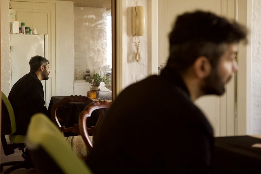 A man sits in his house. His side profile is reflected in a mirror behind him.