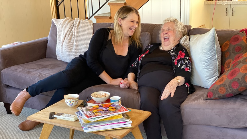 A younger woman and an older woman sit on the couch together, laughing.