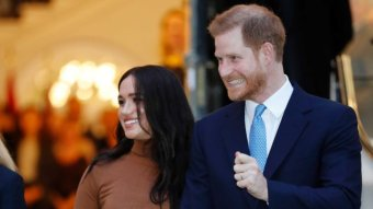 Prince Harry and Meghan smile.