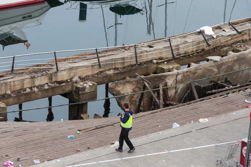A police officer takes a photograph at the scene of a boardwalk collapse