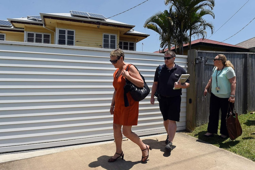 Officials from the Department of Education and Training leave a Moorooka house used as a family daycare