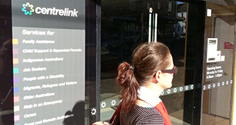 A woman walks past a Centrelink office in Marrickville.