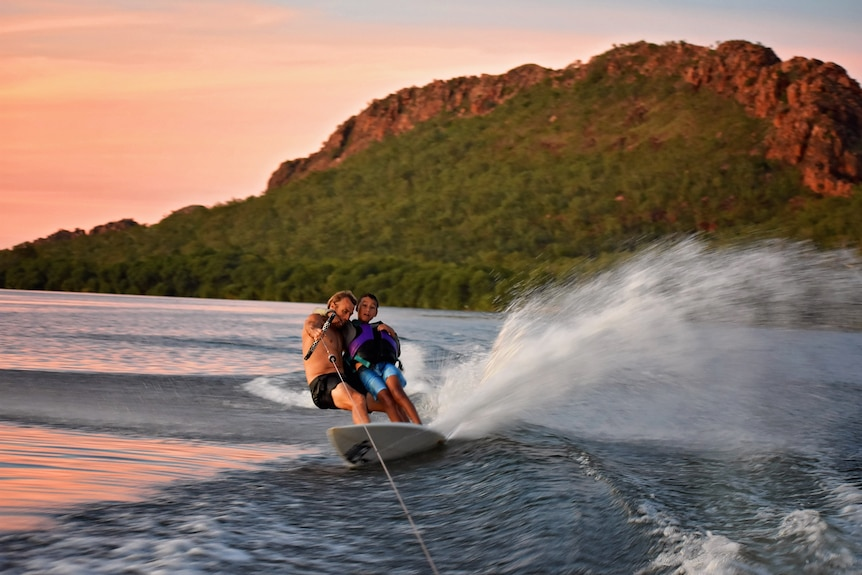 Man with younger boy on surfboard being towed behind boat, with hills in background.