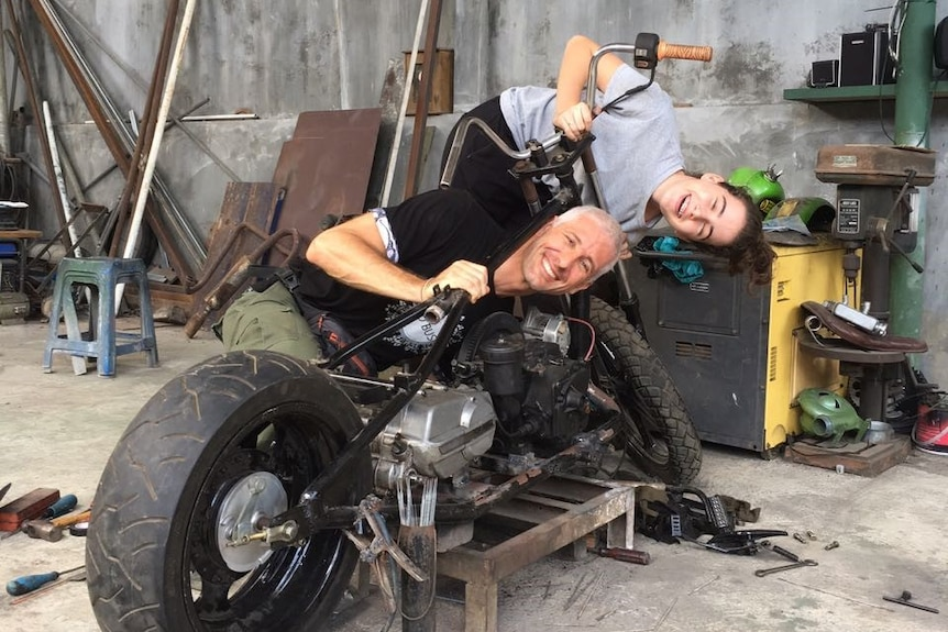 A smiling man and a girl leaning on a motorbike