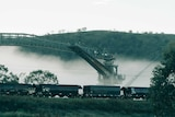 A line of coal train carriages in front of a coal washer machine which is partially covered in fog.