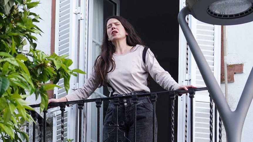 A woman wearing tan shirt and black pants, with long black hair, at a balcony with closed eyes and open mouth as if singing.