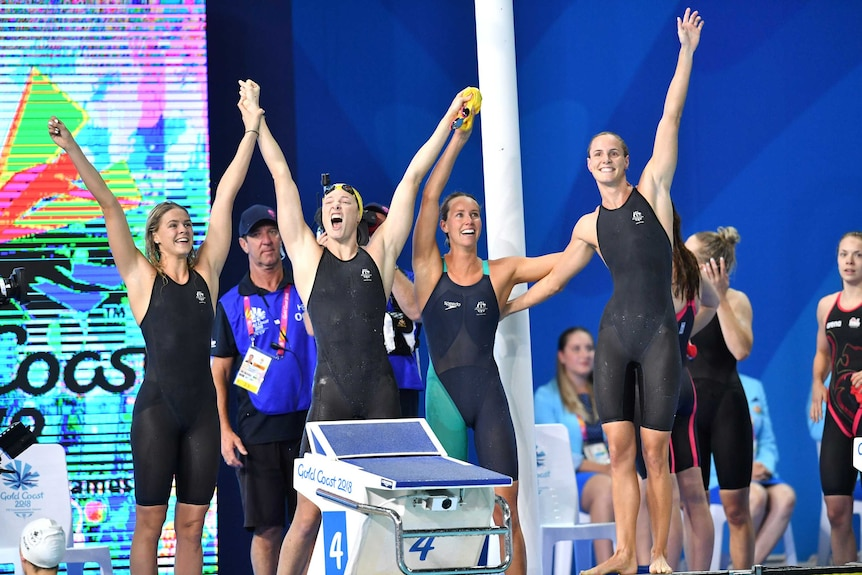 Four female swimmers in black swim suits raise their hands in the air and cheer after a win