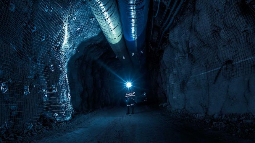 Gold mine worker standing underground in the dark illuminated by head lamp.
