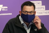 Victorian Premier Daniel Andrews arrives in a mask to speak to the media during a press conference in Melbourne