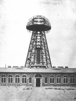 A black and white photo of a dome-topped steel tower above a brick building
